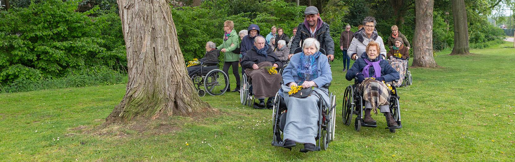 bewoners wandelen door natuur met vrijwilligers