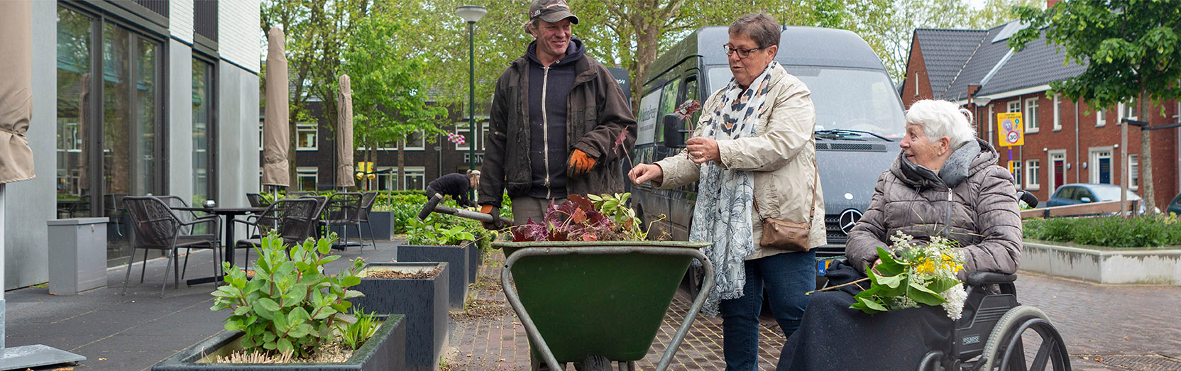 bewoners tuinieren met vrijwilligers